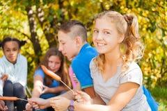 La fille et les ados s'asseyent sur le terrain de camping avec des saucisses Images stock