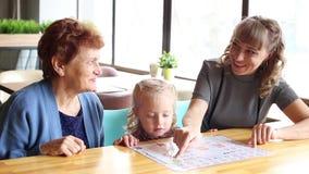 La fille et la petite-fille de la grand-mère observant le menu dans un café clips vidéos