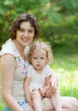 La fille et sa mère détendent en parc photo libre de droits
