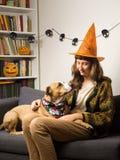 La fille et son chien au sofa dans le salon habillé pour Halloween font la fête Image stock