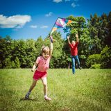 La fille et son père jouent avec un cerf-volant Photos libres de droits