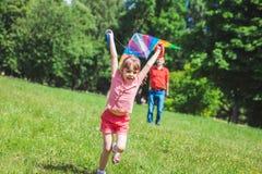 La fille et son père jouent avec un cerf-volant Photos stock