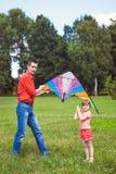 La fille et son père jouent avec un cerf-volant Photographie stock libre de droits
