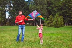 La fille et son père jouent avec un cerf-volant Image stock