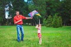 La fille et son père jouent avec un cerf-volant Image libre de droits