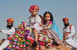 La fille et un garçon montent sur un chameau dans la foule des soldats Ràjasthàn Photographie stock libre de droits