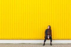 La fille européenne dans une veste en cuir, s'assied près d'un mur et d'un regard au côté photos stock
