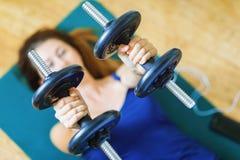 La fille exécute un exercice avec des haltères sur une couverture pour le yoga photos stock