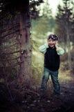 La fille exécute vers le haut d'un arbre dans un gilet dans les bois Image stock