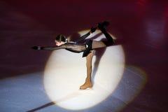 La fille exécutent à de jeunes sportives montrent un tir iceskating Photographie stock libre de droits