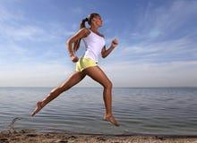 La fille exécutent sur la plage Photos stock