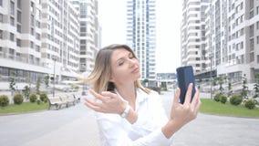 La fille examine le téléphone sur la rue et rectifie ses cheveux clips vidéos