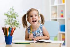 La fille expressive d'enfant dessine se reposer à la table dans la chambre dans la crèche photo stock