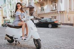 La fille fabuleuse s'assied sur la moto blanche et regarde vers le bas Elle pose sur l'appareil-photo Elle se tient au milieu de Photographie stock libre de droits