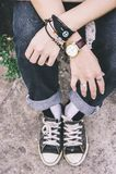 La fille faisante de la planche à roulettes de style, habillant des jeans d'espadrilles dénomment des bijoux Image stock