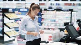 La fille fait l'achat avec la banque ou la carte de crédit, emploie la puce électronique, mouvement lent banque de vidéos