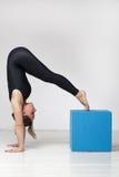 La fille fait l'asana inversé compliqué, faisant le yoga image stock
