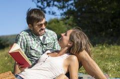 La fille fait la pause à partir de la lecture et regarde son ami Images stock