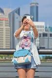 La fille fait le selfie au boulevard de Bund avec des gratte-ciel sur le fond, Changhaï, Chine Photos stock