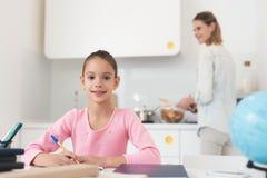 La fille fait les leçons tandis que la maman prépare le dîner Image stock