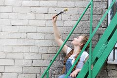 La fille fait la préparation à peindre un belvédère extérieur en bois, barrière images libres de droits