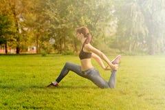 La fille fait un échauffement sur la lumière du soleil, pelouse verte Dans un pleasa photo stock
