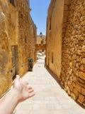 La fille fait un guesture bienvenu sur la vieille rue étroite de Victoria, Malte photos stock