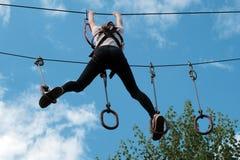 La fille fait un pas d'un anneau à l'autre sur une bande des obstacles au-dessus des arbres contre le ciel avec des nuages Divert Photo stock