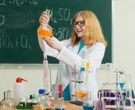 La fille fait une expérience chimique dans une leçon de chimie image libre de droits