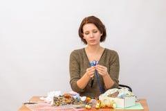 La fille fait une fleur des rubans décoratifs à la table avec la couture Photos libres de droits
