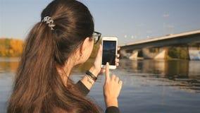 La fille fait une photo au téléphone Belle nature Rivière avec un pont Jour ensoleillé Mouvement lent banque de vidéos
