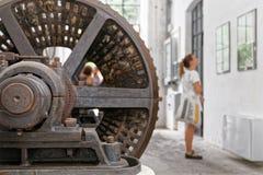 La fille a fasciné des documents de loi sur la vieille usine, derrière elle un tambour énorme de dessiccateur image stock
