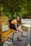 La fille fascinante d'affaires avec un sac repose, redresse les chaussures sur son pied sur un banc de parc image libre de droits