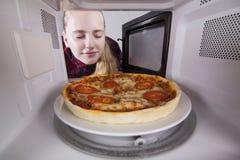 La fille fermant ses yeux reniflant l'arome de la pizza a fait cuire dans la micro-onde photographie stock