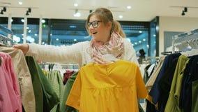 La fille folle faisant des achats en vente au grand centre commercial, les achats shopaholic femelles vêtx du magasin, variété de banque de vidéos