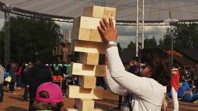 La fille font la tour à partir des briques en bois avec le père adulte Festival de famille d'été banque de vidéos
