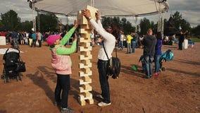 La fille font la tour à partir des briques en bois avec le papa adulte Festival de famille d'été banque de vidéos