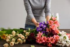 La fille font le bouquet au-dessus du fond gris Images stock