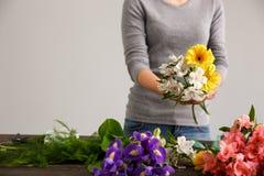 La fille font le bouquet au-dessus du fond gris Photographie stock
