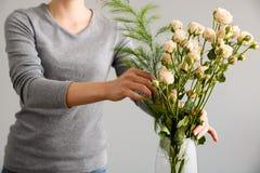 La fille font le bouquet au-dessus du fond gris, mettant fleurit dans le vase Image libre de droits