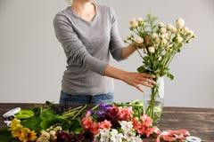 La fille font le bouquet au-dessus du fond gris, mettant fleurit dans le vase Photographie stock libre de droits