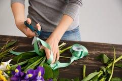 La fille font un bouquet au-dessus du fond gris, coupant le ruban Photographie stock libre de droits