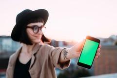La fille fraîche à la mode de hippie tient le téléphone de clé de chroma Images stock