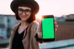 La fille fraîche à la mode de hippie tient le téléphone de clé de chroma Photographie stock libre de droits