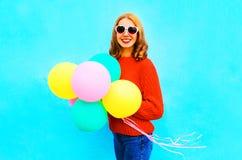 La fille fraîche tient les ballons à air colorés sur le bleu Photos stock