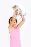 La fille gaie d'enfant joue avec un petit chaton sur un fond clair Photo stock