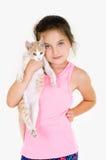 La fille gaie d'enfant joue avec un petit chaton sur un fond clair Photographie stock