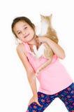 La fille gaie d'enfant joue avec un petit chaton sur un fond clair Photos stock