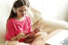 La fille gaie dans des écouteurs roses s'assied avec un téléphone dans sa main et une carte de crédit photo stock
