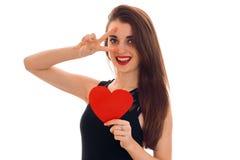 La fille gaie de brune dans la robe noire avec gentil composent pour célébrer le jour de valentines avec le coeur rouge dans des  Photo stock